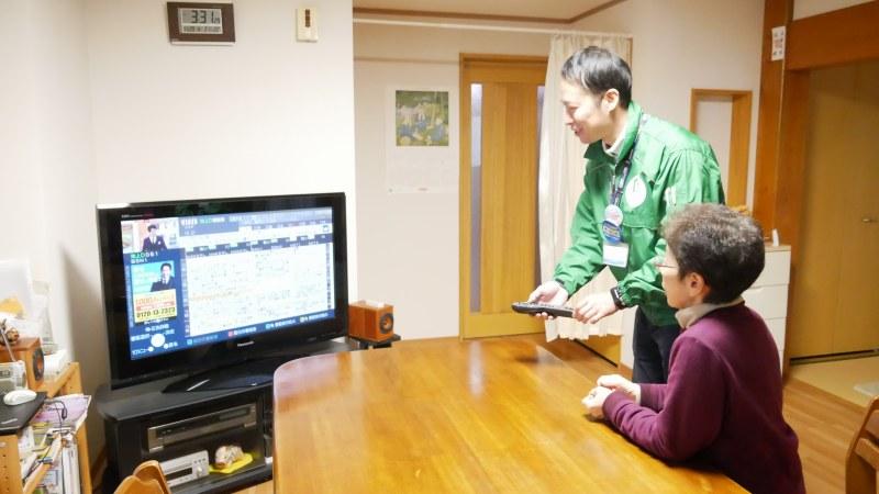 テレビの操作方法を説明するスタッフ